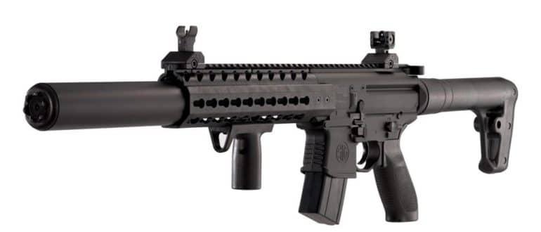 Оружейная фирма Sig Sauer достаточно старая и на международном рынке оружия хорошо известная. Однако эта компания выпускает не только первоклассное огнестрельное оружие, но и замечательное пневматическое оружие, которое по внешнему виду в точности копирует огнестрельные образцы. Sig Sauer стала выпускать пневматическое оружие в 1990-х годах, когда спрос на пневматику значительно вырос и многие фирмы конкуренты стали захватывать эту нишу оружейного рынка. Sig Sauer не могла этого допустить, что разумеется правильно и разработала и запустила в производство пневматику, похожую на свои лучшие модели огнестрельного оружия. Этот маркетинговых ход был абсолютно верным: пневматические винтовки (и не только ) Sig Sauer MCX пользуются огромным спросом: они не только очень похожи на штурмовую винтовку Sig Sauer АР-15, но и снаряжаются как и старший оригинал, оптикой, коллиматорными прицелами и другими приспособлениями, что безусловно лишь повышает популярность пневматики Sig Sauer MCX. Своё пневматическое оружие фирма Sig Sauer продает по всему миру, в том числе и в России. На это оружие не требуется каких-либо разрешений и лицензий. Технические характеристики и внешний вид Sig Sauer MCX. Как уже говорилось, Sig Sauer MCX полностью точная копия боевой штурмовой винтовки, то есть у этой пневматики есть отсоединяемый магазин на тридцать пулек, есть автоматический затвор, есть предохранитель, есть пистолетная рукоятка как у боевой винтовки. В прикладе расположен газовый баллон, который и позволяет совершать выстрелы. Ствол бывает длиной 35 см. или 50 см., в зависимости от модификации, но независимо от этого, ствол имеет нарезы для более лучших показателей кучности и точности выстрела. Калибр 4,5 мм. Для стрельбы используются свинцовые пульки, либо пульки с хвостовиком и в оболочке. Начальная её скорость достигает 250 м/сек., что вполне пригодно для охоты на пернатую дичь. Дульная энергия до 7,5 Дж., что позволяет приобретать такую винтовку, предоставив только паспорт. Никаких спе